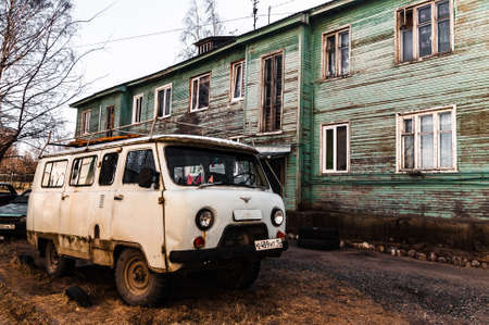 Petrozavodsk, Russia - 17 March 2020. old gray UAZ-452 next to a green two-story barracks Редакционное