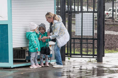Petrozavodsk, Russia - 1 August 2020. family hiding from heavy rain in amusement park