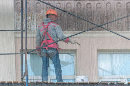 Petrozavodsk, Russia - 17 August 2020. a worker paints the facade of the building. View through the safety net