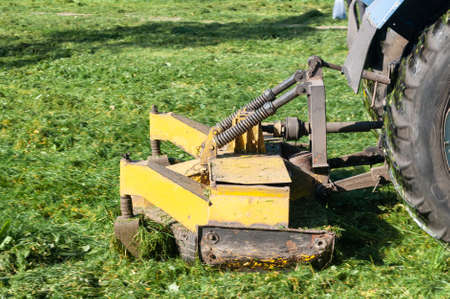 close up of tractor mows the grass on the lawn in the city yard