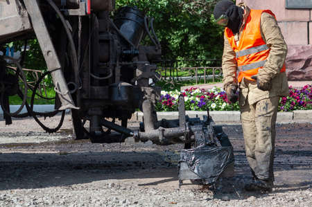 the process of preparing for the laying of new asphalt. machine pouring bitumen Фото со стока