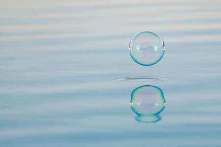 Abstract background with water surface and bubble bouncing off it Фото со стока