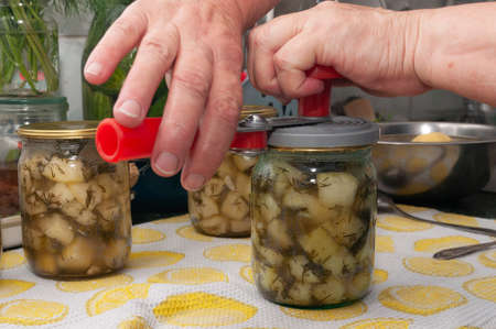 cooking canned vegetables. close up of hands are rolling up the lids with can sealing machine Фото со стока - 157131798