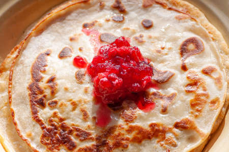 Russian pancakes on plates decorated with berry jam Фото со стока