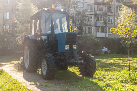 tractor on a footpath in the city on a sunny afternoon Фото со стока
