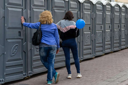 view from the back of two women standing at a row of biotoilets Фото со стока