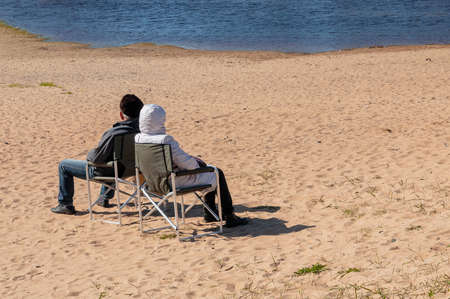 The couple sits on folding chairs on the beach on a sunny cold afternoon.