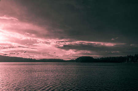 beautiful tinted landscape with sunset over a forest lake