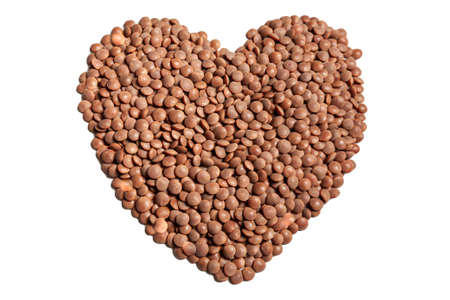 brown lentil beans in shape of heart isolated on white background