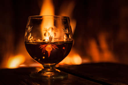glass with alcohol, cognac or whiskey, standing against the background of fire in the fireplace
