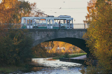 autumn landscape with woman on the bridge and passing trolley bus in motion blur