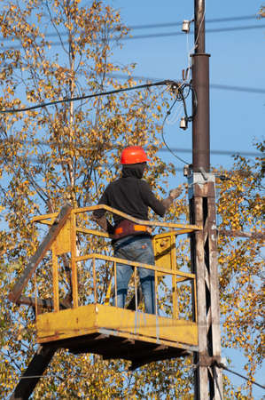 a worker on a lifting platform paints a pole