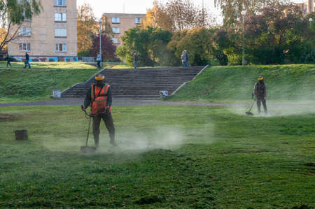 two workers mow the lawn in the morning Редакционное