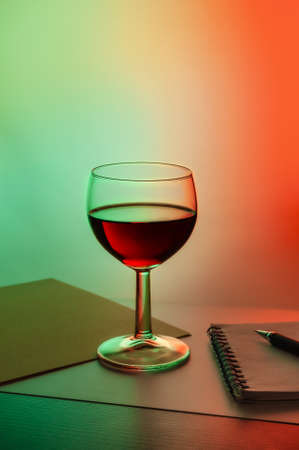 a glass of red wine on a background with red green lighting. High quality photo