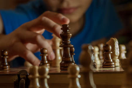 A boy plays chess. Focus on the foreground. High quality photo Фото со стока