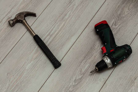 View from above on the hammer and drill lying on a wooden background. High quality photo Фото со стока