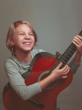 little girl with guitar on gray background. High quality photo Фото со стока