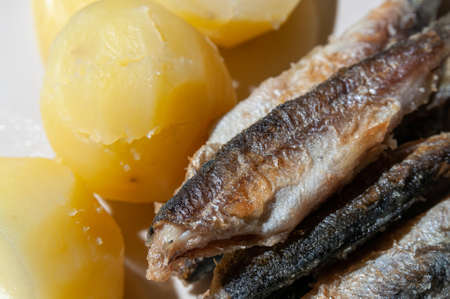 Top view of small fried fish and boiled potatoes on a plate. High quality photo