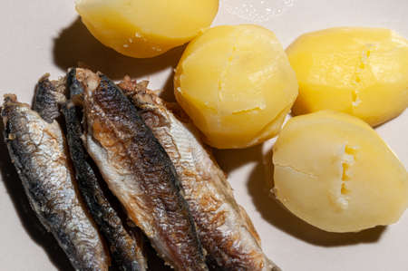 close-up of small fried fish and boiled potatoes. High quality photo