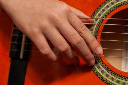 close up of woman's hand playing guitar. High quality photo