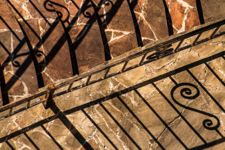 abstract background with shadows from the forged fence and stone steps