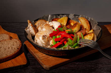 Baked chicken with potatoes and vegetables in a cast-iron frying pan. Фото со стока