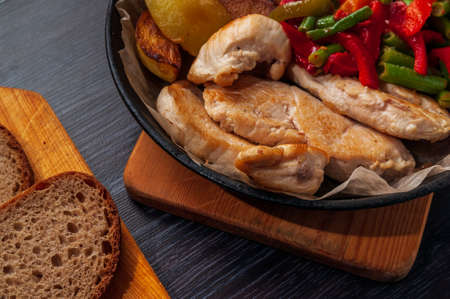 baked chicken, potatoes and vegetables in a cast-iron frying pan.