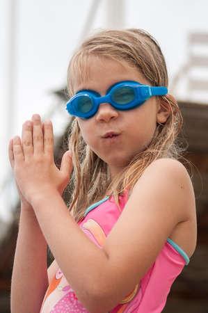 Cute girl in swimming glasses and swimsuit, going to dive into the water