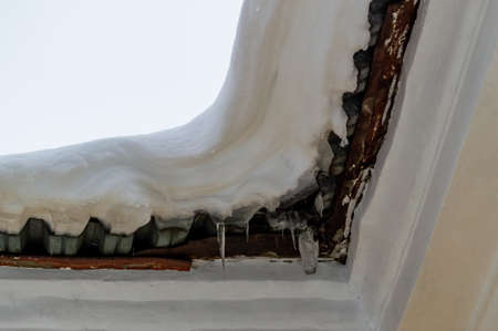 snow cap and icicles on the roof of the building