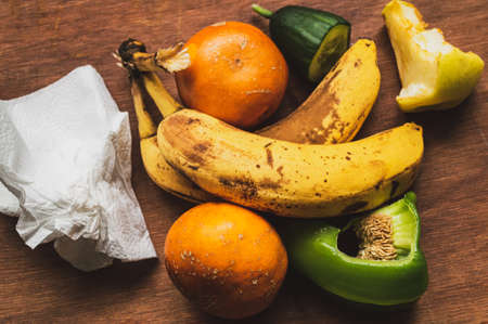 ugly fruits and vegetables. darkened bananas, mandarines and apple core, slices of cucumber and pepper.