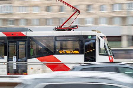Saint Petersburg, Russia - 2 February 2021. White red modern tram on city street. Motion blur