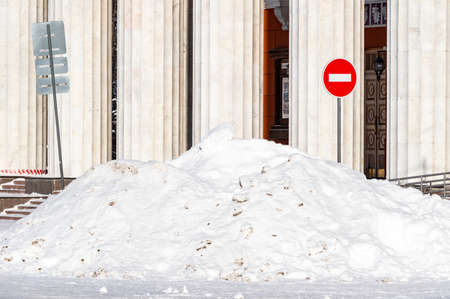 a large pile of snow in front of a building with columns. High quality photo