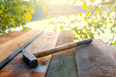hammer and nail on boards. Sun flare. Building a treehouse. High quality photo Фото со стока