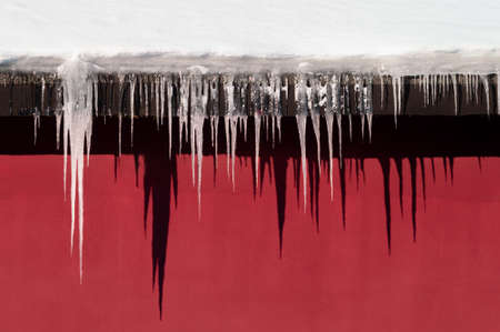 Background with icicles of different lengths casting shadows on the wall. High quality photo