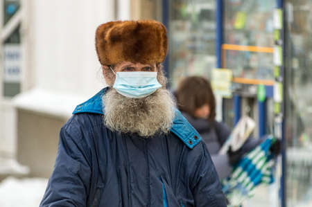 portrait of an elderly bearded man in a medical mask and a fur hat