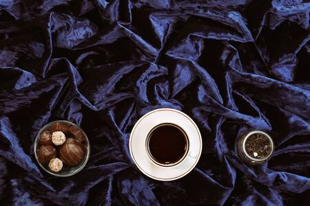White porcelain cup with tea and sweets in a candy bowl on a velor surface with fabric cloths. View from above. Top view.Black and green tea brewed