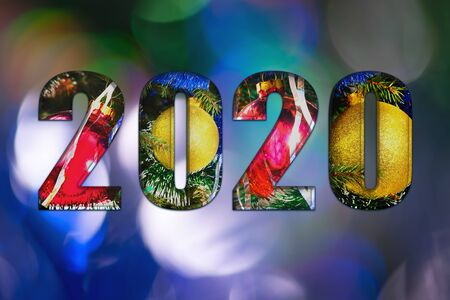 2020. New year background. The numbers 2020. Christmas decoration. Christmas background.Christmas toys, red and yellow balls on a bokeh background with blue and green colors. Copy space Banco de Imagens