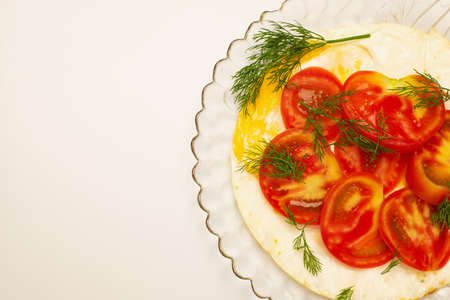Eggs and chopped tomatoes on top with dill greens on a transparent glass plate isolated on white . Top view