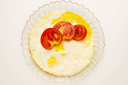 Eggs and several chopped tomatoes on top on a transparent glass plate isolated on white.Top view Stock fotó