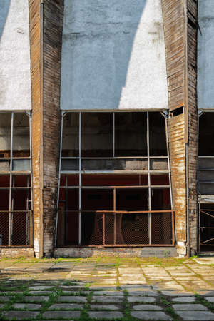 Collapsing facade of an industrial abandoned building with a glass facade and partially broken glass
