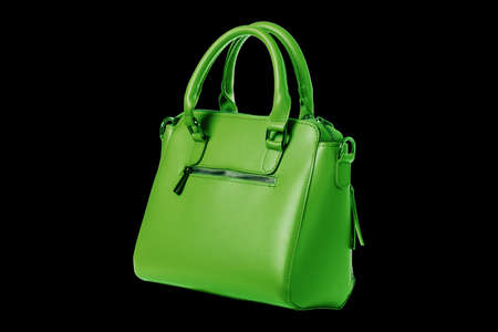 Green leather women's bag with top handle isolated on black background. Front view of a lady shopping bag. Ladies top handle short and fasteners for long handle