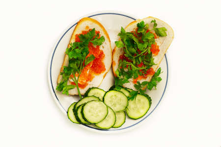Red salmon caviar laid out with parsley on bread slices with butter and cucumber rings on a white plate isolated on white. Gourmet food top view