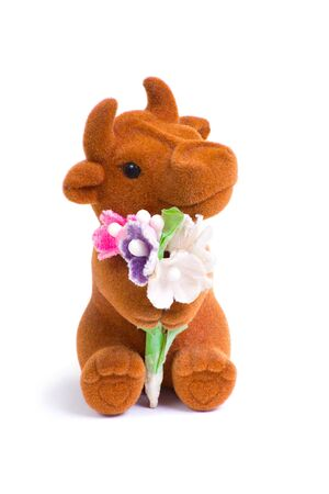 Front shot of cute little loved bull toy with bouquet of flowers photo