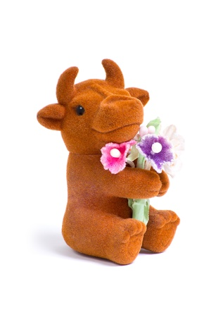 Side macro shot of cute little loved bull toy with bouquet of flowers photo