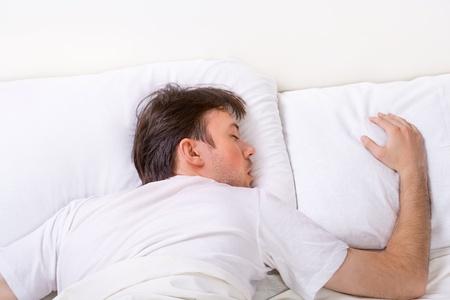 durmiendo: El hombre duerme en la cama con el sue�o muy profundo Foto de archivo
