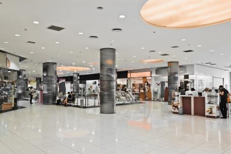 tienda de ropa: Interior del moderno centro comercial con algunas personas en el mismo Editorial