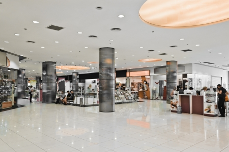 Interior of modern mall with some people in it Редакционное