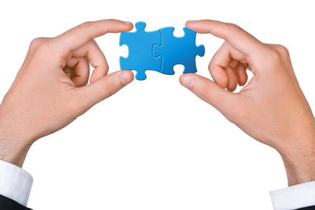two pieces: Concept of teamwork - hands connect two puzzle pieces
