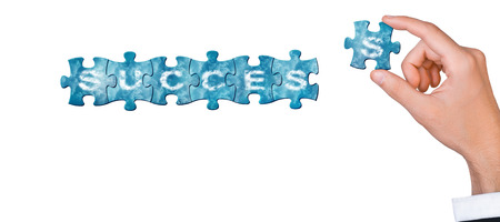 Concept of success - hand connects puzzle piece to build word success photo