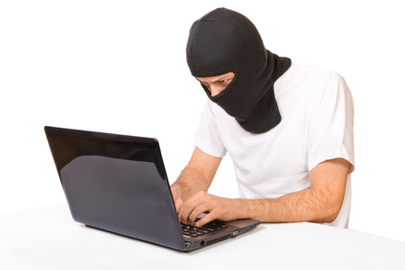 Side shot of man in black mask looking at monitor and typing something photo